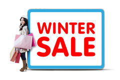 Female shopaholic lean on winter sale text Royalty Free Stock Image