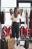 female shopaholic with shopping bags and clothes in boutique with sale tags, black royalty free stock images