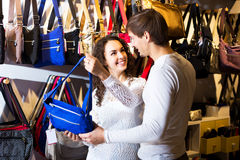 Female shopgirl helping young man to select handbag Royalty Free Stock Images