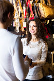 Female shopgirl helping young man to select handbag Stock Photography