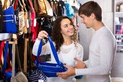 Female shopgirl helping young man to select handbag Stock Photo