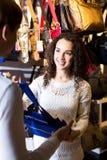 Female shopgirl helping young man to select handbag Stock Images