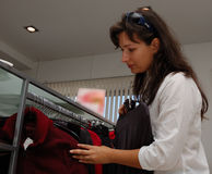Female shopper. A woman shopping for clothes looks through garments hung on a rack inside a store Royalty Free Stock Photography