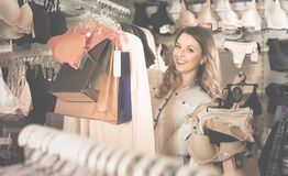 Female shopper boasting her purchases in underwear shop Royalty Free Stock Photos