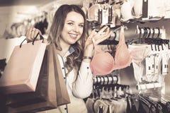 Female shopper boasting her purchases in underwear shop Stock Photo