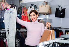 Female shopper boasting her purchases in women's cloths shop Stock Image