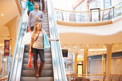 Female Shopper On Escalator In Shopping Mall. Holding Bags Smiling Royalty Free Stock Photos