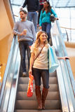 Female Shopper On Escalator In Shopping Mall. With People Behind Looking Away From Camera Royalty Free Stock Image