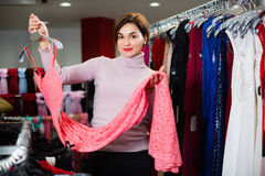 Female shopper examining dresses in women's cloths shop Stock Photography
