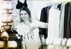 Female shopper examining long sleeve shirts in underwear shop Royalty Free Stock Images