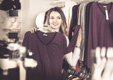 Female shopper examining long sleeve shirts in underwear shop Royalty Free Stock Photography