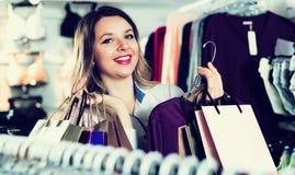 Female shopper examining long sleeve shirts in underwear shop Stock Photo