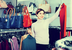 Female shopper examining turtleneck sweaters in women's cloths Royalty Free Stock Photos
