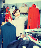 Female shopper examining turtleneck sweaters in women's cloths Royalty Free Stock Images