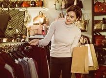 Female shopper examining warm sweaters in women's cloths shop Stock Photos