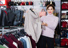 Female shopper examining warm sweaters in women's cloths shop Stock Images