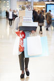 Female Shopper Hidden Behind Boxes Shopping In Mall Stock Image