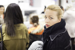 Female shopper queuing in line at cashier. Woman shopping clothes. Shopper queuing in line at cashier in textile store. Beautiful blonde caucasian female model Stock Image