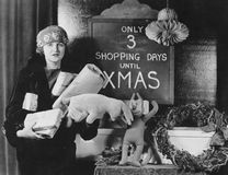 Female shopper and sign with number of shopping days until Christmas. (All persons depicted are no longer living and no estate exists. Supplier grants that Stock Images