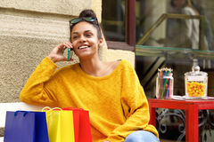 Female shopper sitting outdoors and using mobile phone Stock Image