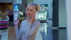 Female shopper talks on the phone at the mall stock footage