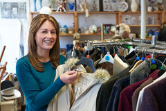 Female Shopper In Thrift Store Looking At Clothes Royalty Free Stock Photo
