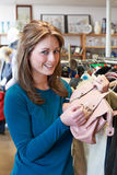Female Shopper In Thrift Store Looking At Handbag Royalty Free Stock Image