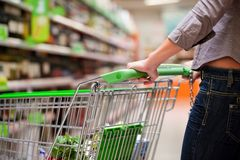 Female Shopper With Trolley at Supermarket Stock Photos