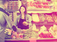 Female shopping assistant helping customer to buy fruit and vege Stock Photo