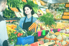 Female shopping assistant helping customer to buy fruit and vege Stock Images