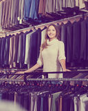 Female shopping assistant offering various suits in men's clot Royalty Free Stock Photo