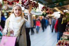 Female shopping at festive fair. Happy beauty female shopping at festive fair before Xmas Stock Photo