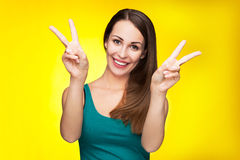Female showing peace sign. Casual young woman over yellow background Royalty Free Stock Images