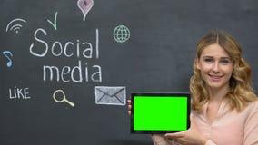 Female showing prekeyed tab standing on blackboard background using social media. Stock footage stock video