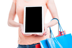 Female showing tablet blank screen and holding shopping bags Stock Photography