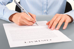 Female signing contract at desk. Royalty Free Stock Images