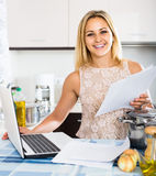 Female signing documents at the kitchen Stock Images