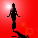 Female silhouette. An image showing an illustration of a female as a black silhouette against a lens flare red background Stock Image