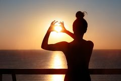 Female Silhouette at the Balcony Making Heart Sign Gesture. Woman in love expressing her feelings and hopes stock image