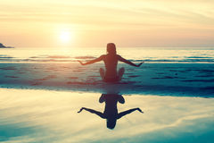 Female silhouette doing exercise at beautiful sunset on the sea beach Stock Photos
