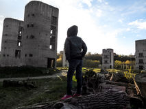The female silhouette in the hood stands in front of the ruined buildings - the view from the back Stock Photos