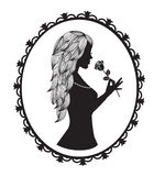 Female silhouette with long hair holds a rose. In a retro frame Royalty Free Stock Photos