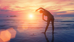 Female silhouette performs physical exercises on the beach after sunset. Fitness. Stock Image
