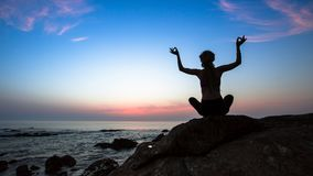 Female silhouette practicing yoga on the ocean cliff beach Royalty Free Stock Photo