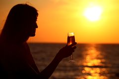 Female silhouette on sea sunset with glass Royalty Free Stock Photo