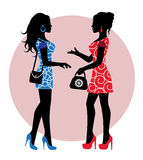 Female silhouette stand and talk. Two female silhouette in dresses and with bags stand and talk Royalty Free Stock Photography