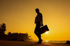 Female Silhouette staying along Ocean Coast with Luggage Bag enj Stock Photography