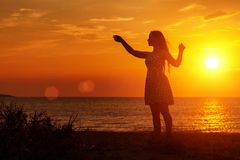 Female silhouette at sunset on the beach, hands up royalty free stock photography