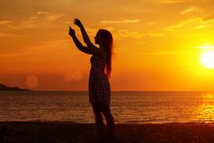 Female silhouette at sunset on the beach, hands up stock image