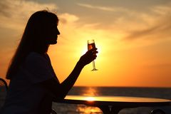 Female silhouette on sunset with glass in hand Royalty Free Stock Photos